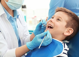 happy toddler boy opening mouth for dental hygienist