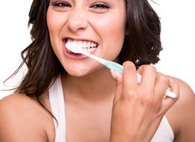 attractive woman brunette hair brushing teeth