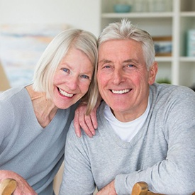 elderly couple wearing gray sweaters and smiling with dental implants in Acworth