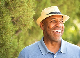 older man in blue polo and fedora smiling amongst trees