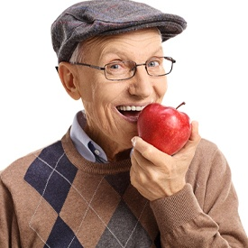 An older man biting into an apple.