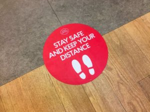Sign on floor asking visitors to practice social distancing