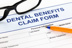 Dental benefits claim form with glasses and ballpoint pen.