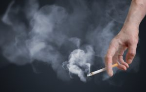 Smoker holding smoking cigarette in hand